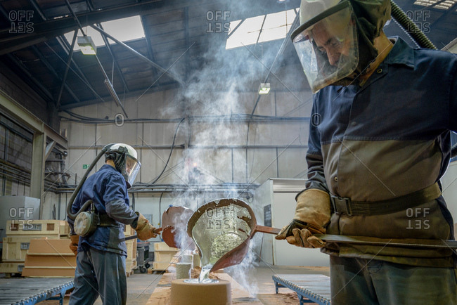 Workers pouring molten aluminum into moulds in precision casting factory