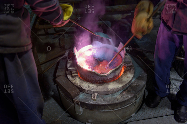 Workers stirring molten aluminum alloy in precision casting factory