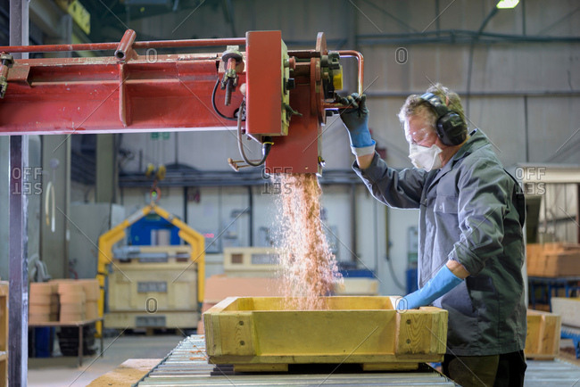 Worker pouring sand into mould in precision casting factory