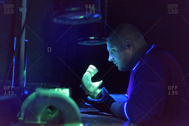 Worker using ultra-violet light to test for cracks in components in precision casting factory