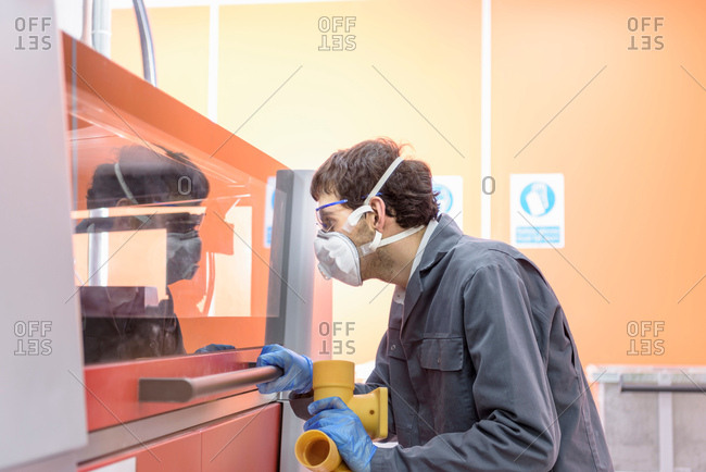 Worker 3D printing components in precision casting factory