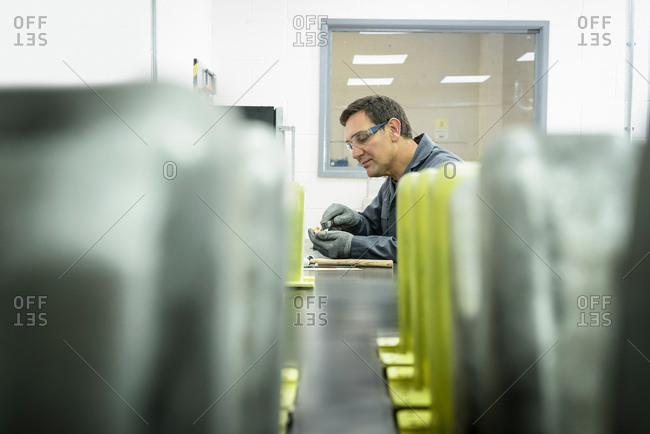 Worker finishing components in precision casting factory