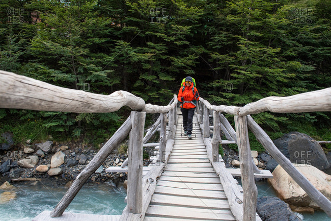 Female hiker crossing wooden bridge on the way up to Torres del Paine National Park, Patagonia, Chile