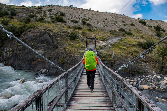Female hiker crossing a suspension bridge on the way up to Torres del Paine National Park, Patagonia, Chile