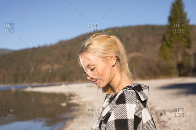 Young woman on lakeside looking down, Bavarian Alps