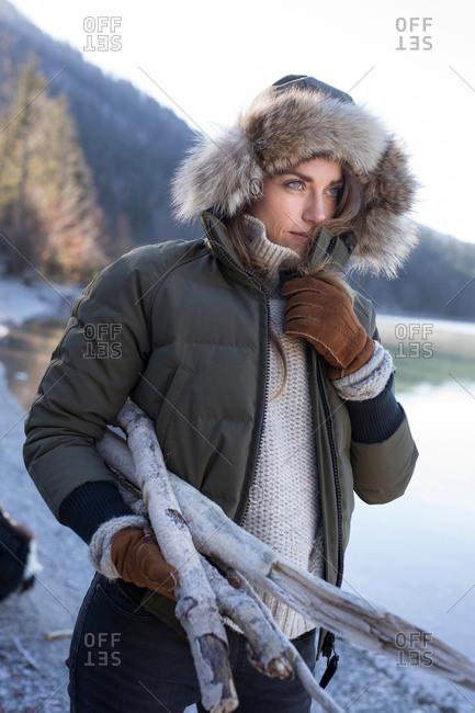 Woman in fur trim hood carrying firewood on lakeside in Bavarian Alps
