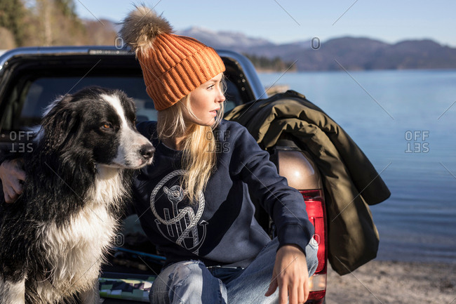 Young woman and dog looking out from pick up on lakeside in Bavarian Alps