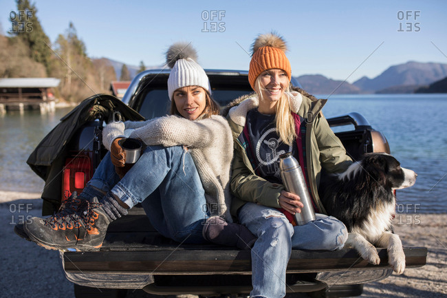 Two women with coffee and dog sitting on pick up at lakeside in Bavarian Alps