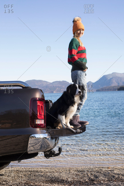 Young woman and dog standing on pick up at lakeside in Bavarian Alps