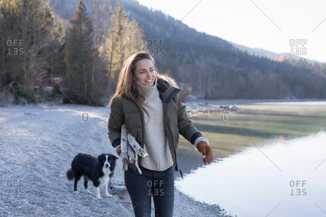 Woman walking dog on lakeside in Bavarian Alps