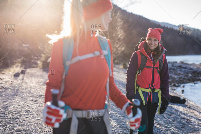 Two female hikers hiking on lakeside in Bavarian Alps