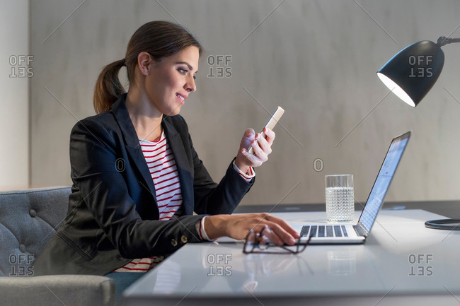 Young businesswoman at desk using laptop and looking at smartphone
