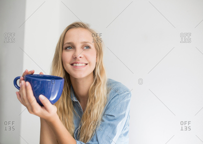 Portrait of young woman with long blond hair holding coffee cup