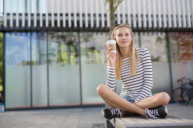 Portrait of young woman sitting cross legged on city bench with takeaway coffee