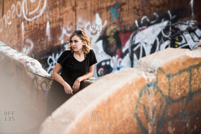 Young woman leaning against graffiti wall mine ruins