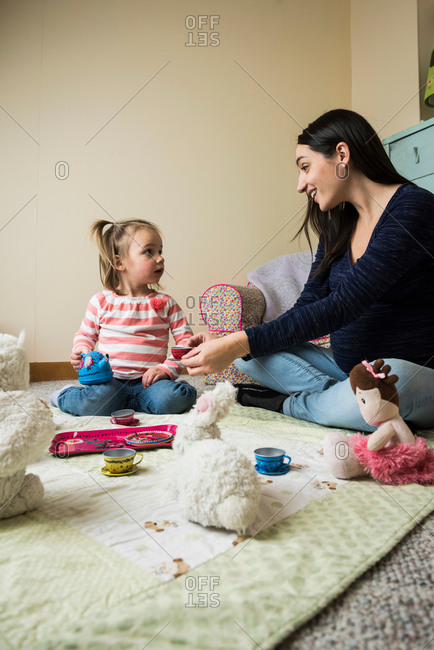 Female toddler sitting on floor with pregnant mother playing picnics with soft toys