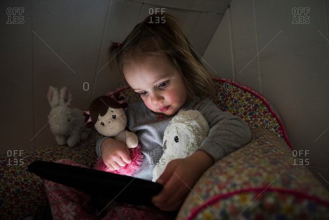 Female toddler sitting up in bed staring at digital tablet