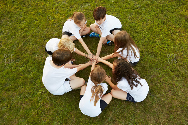 Overhead view of boy and girl sport team sitting on grass in circle on playing field