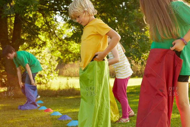 Girls and boys preparing for sack race on start line in park