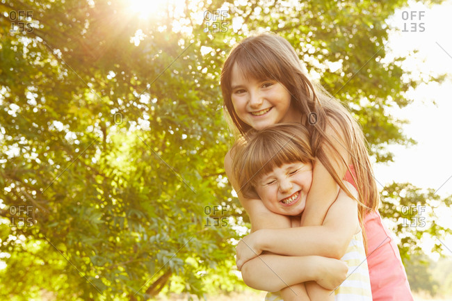Portrait of girl being hugged by big sister in park