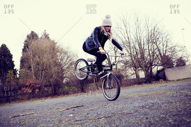 Female bike rider doing bike trick on wasteland