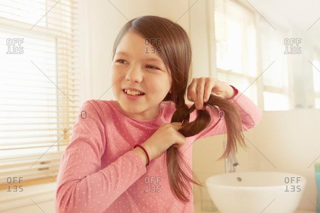 Girl plaiting long brown hair in bathroom