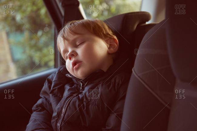 Male toddler asleep in car backseat