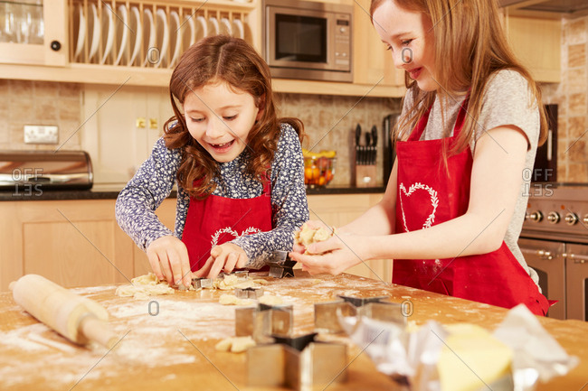 Two girls making star shape pastry at kitchen table
