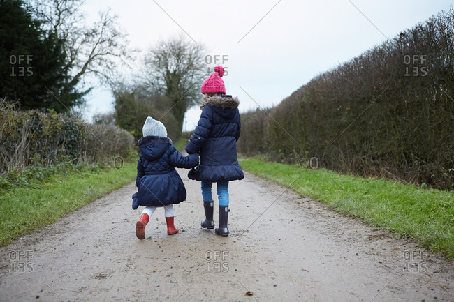 Rear view of girl and female toddler in knit hats walking along rural road