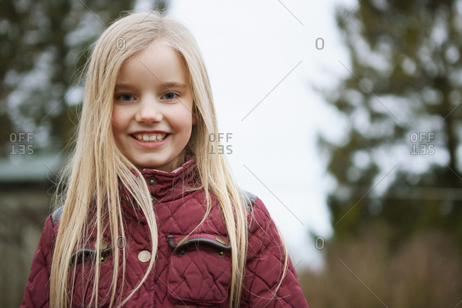 Portrait of girl with long blond hair outdoors