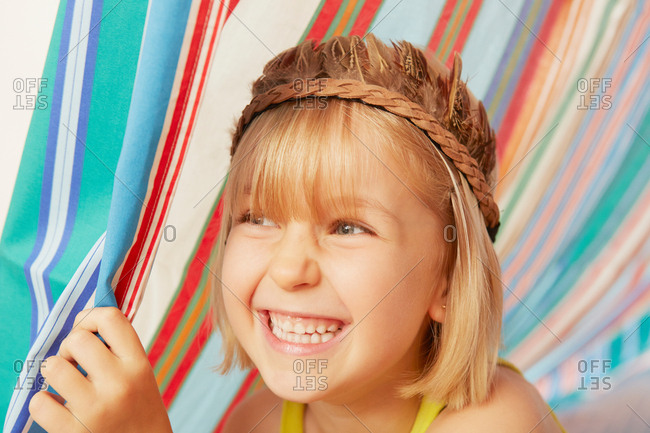 Smiling girl peeking out from striped tent