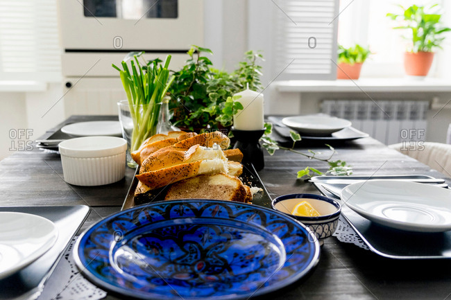 Set kitchen table with bread slices, fresh herbs and spring onions