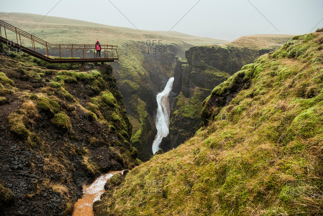 Tourist on footbridge looking out at canyon waterfall, Fjadrargljufur, Iceland