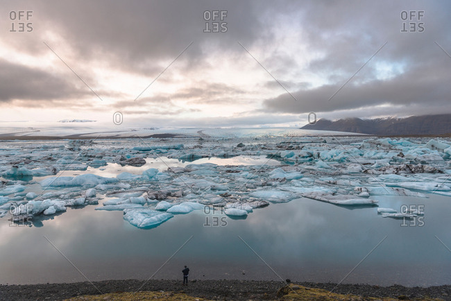 High angle view of tourist looking out at icebergs on glacial lagoon, Jokulsarlon, Iceland