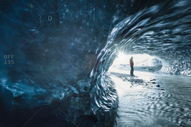 Male tourist in ice cave at Breidamerkurjokull, Iceland