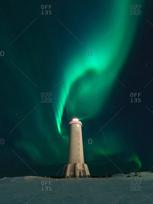 Aurora borealis swirling green over lighthouse at night,   Akranes, Iceland