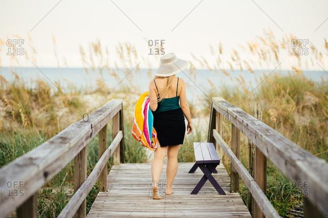 Rear view of young woman strolling to sea on boardwalk, Carolina Beach, North Carolina, USA