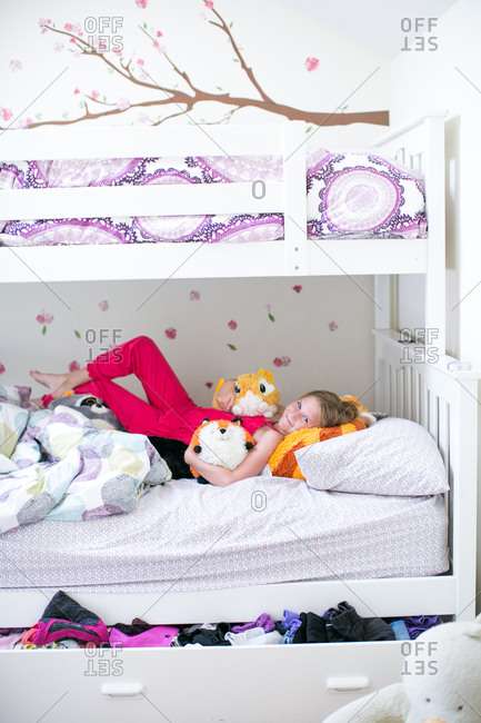 Portrait of girl lying on bunk bed with soft toys