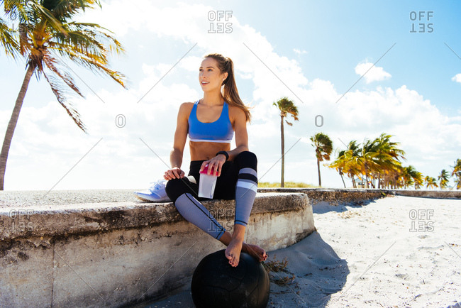 Young female runner sitting with takeaway drink on beach wall