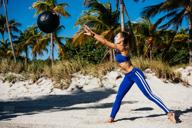 Young woman training, throwing exercise ball at beach