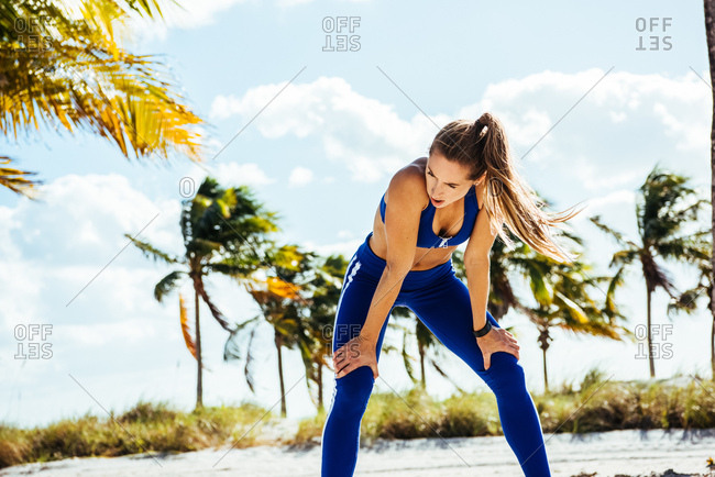 Young woman training, leaning forward exhausted at beach