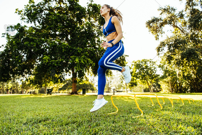 Young woman training, jumping agility hurdles in park