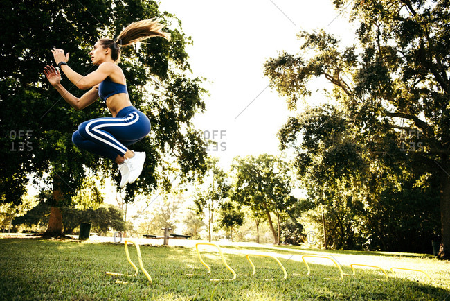 Young woman training, jumping between agility hurdles in park