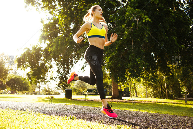 Young female runner running through park