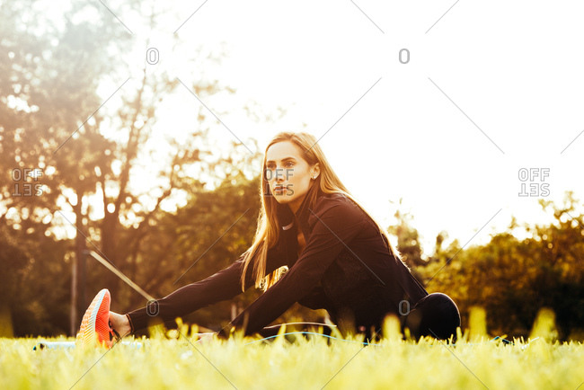 Young female runner touching toes in park