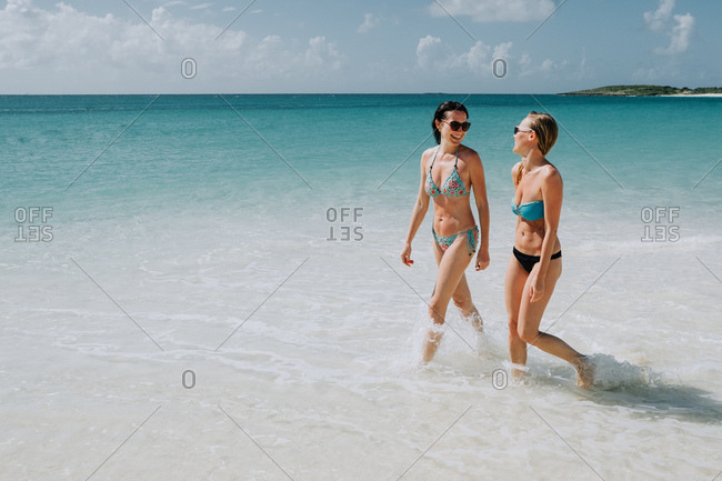 Two mid adult sisters strolling in blue sea, Anguilla, Saint Martin, Caribbean