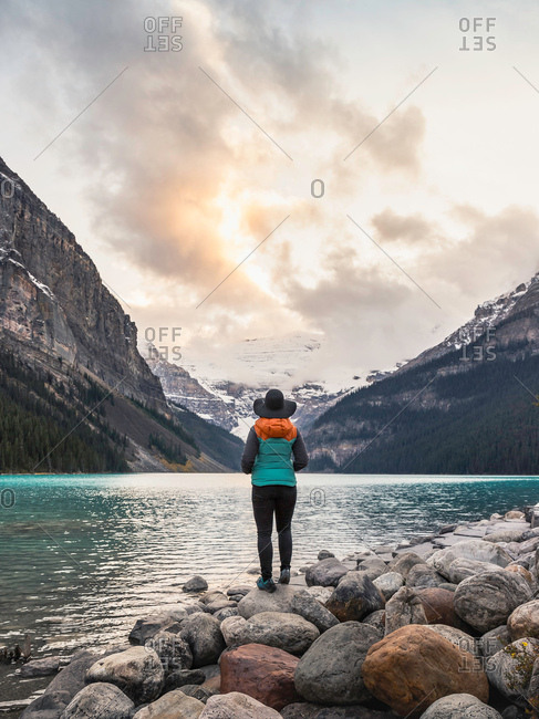 Woman standing at edge of lake, looking at view, rear view, Lake Louise, Alberta, Canada
