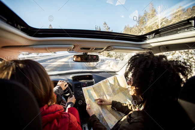 Woman driving car, friend in passenger seat looking at map
