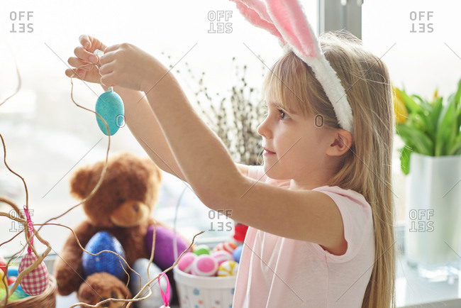 Girl in bunny ears making easter egg decoration in living room
