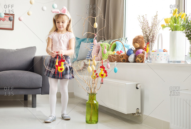 Girl making easter decorations in living room